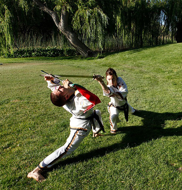 Two people combating with weapons on grass doing Ship Pal Gae